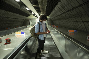 Man wearing protective mask standing on escalator looking at mobile phone, London, UK - PMF01117