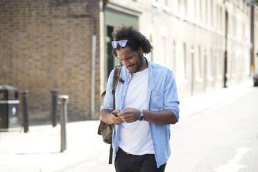 Young man with backpack standing on street looking at cell phone, London, UK - PMF01120