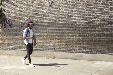 Young man walking on pavement looking at mobile phone, London, UK - PMF01123