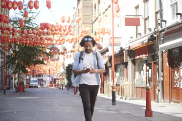 Young man walking on street looking at smartphone, Chinatown, London, UK - PMF01126