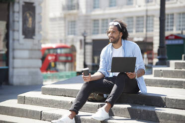 Portrait of smiling young man with coffee to go and laptop sitting on stairs outdoors, London, UK - PMF01129