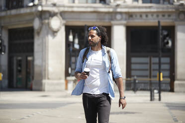 Portrait of young man with coffee to go crossing the street while listening music with earphones, London, UK - PMF01132