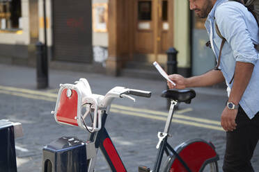 Crop view of man using rental bike in the city, London, UK - PMF01135