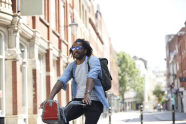 Portrait of young man on rental bike in the city, London, UK - PMF01138