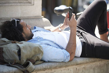 Young man relaxing in the city looking at cell phone, London, UK - PMF01141