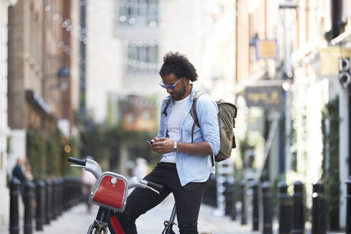 Young man with rental bike and backpack using cell phone in the city, London, UK - PMF01144