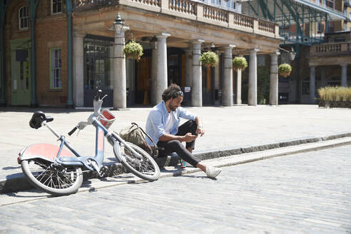 Young man with rental bike and backpack sitting at roadside looking at cell phone, London, UK - PMF01147
