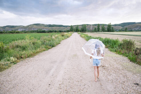 Girl with umbrella walking on dirt road during monsoon - JCMF00913