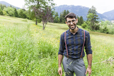 Portrait of smiling young man standing on a meadow, Reichenwies, Oberammergau, Gerrmany - TCF06291