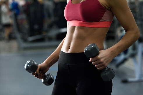 Midsection Of Woman Exercising In Gym - EYF07875