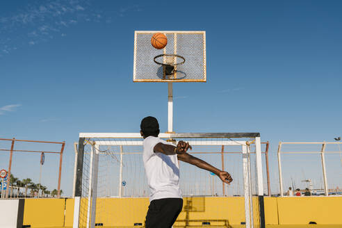 Young man holding basketball while standing against clear blue sky in city during sunny day - EGAF00289