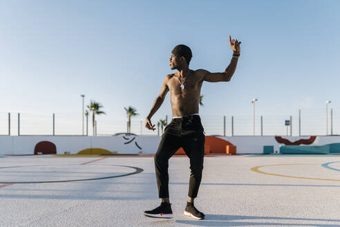 Shirtless young man dancing against clear sky in sports court during sunny day - EGAF00301