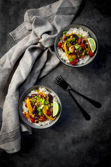 Two bowls of Mexican rice with bell peppers, tofu, kidney beans, tomatoes, corn, lime and scallion - LVF08928