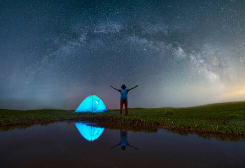Rear View Of Mature Man With Arms Outstretched Standing On Grassy Field By Lake At Campsite Against Star Field - EYF08355