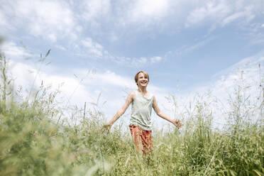 Portrait of happy boy walking on a field - EYAF01180