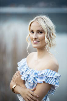 Portrait of smiling blond woman wearing striped top standing in front of Woerthersee, Austria - DAWF01719