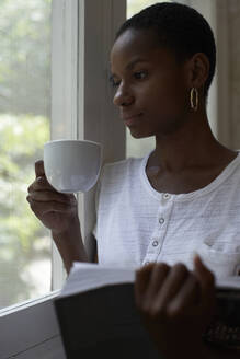 Close-up of thoughtful young woman holding coffee and book while looking through window at home - VEGF02422