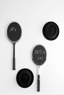 Black hats and blackboards made from tennis rackets hanging on white wall - GISF00621
