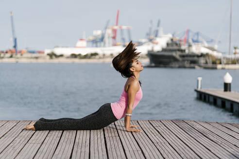 Female athlete with eyes closed practicing cobra pose on pier against sea at harbor - EGAF00318