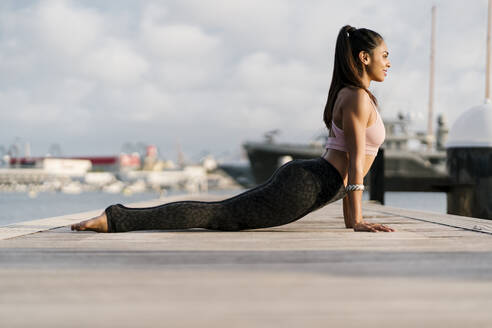 Athlete practicing upward facing dog pose on pier at harbor - EGAF00336
