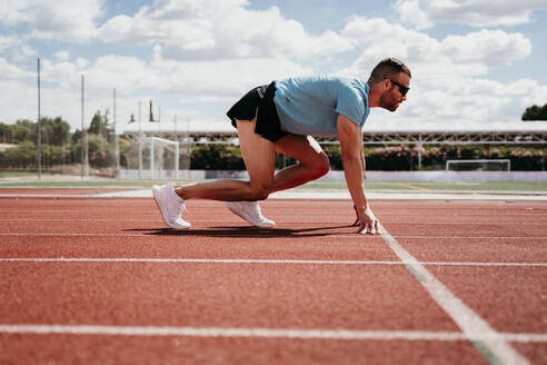 Male athlete in starting position on tartan track - EBBF00218