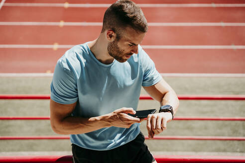 Male athlete in stadium checking smartwatch and smartphone - EBBF00233