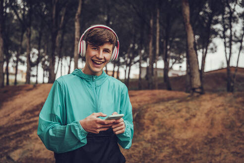 Teenager with headphones wearing raincoat in the forest - ACPF00764