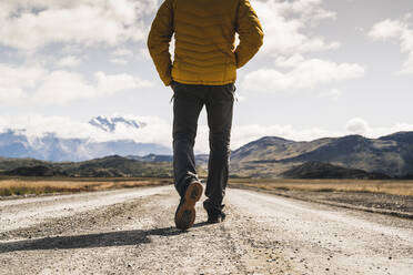 Mature man walking on dirt road against cloudy sky, Torres Del Paine National Park, Patagonia, Chile - UUF20736