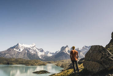 Mature man with backpack walking by lake against sky, Patagonia, Argentina - UUF20739