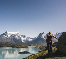 Male hiker looking away while standing against mountains at Patagonia, Argentina - UUF20742