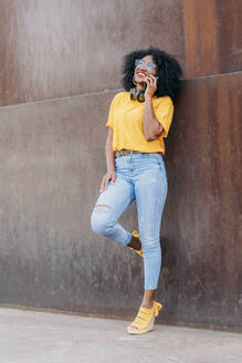 Smiling woman with afro hair and glasses using smartphone leaning on wall - JAF00003