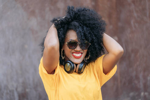Smiling woman with afro hair and sunglasses and hands in hair - JAF00006