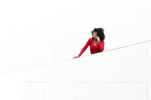 Young woman with afro hair using smartphone on white ramp - JAF00009