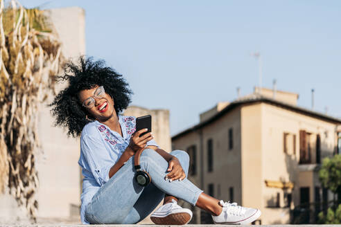 Laughing woman with afro hair and glasses using smartphone - JAF00012