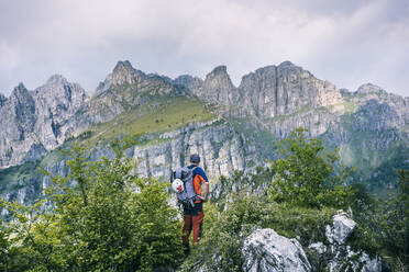 Hiker standing on mountain path enjoying view, Orobie, European Alps, Como, Italy - MCVF00480