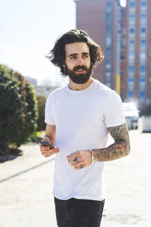 Bearded young man using smart phone while walking on street during sunny day - MEUF01003