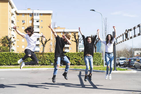Carefree friends with arms raised jumping on road in city on sunny day - MEUF01039