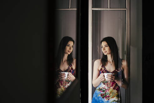 Woman with coffee cup standing against door at home - EBBF00287