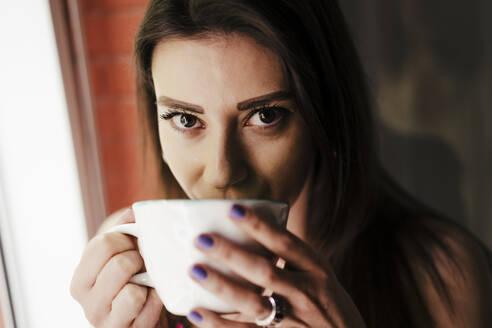 Beautiful woman drinking coffee at home - EBBF00290