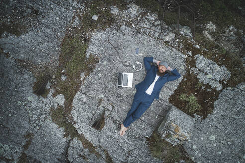 Aerial view of businessman wearing suit with hands behind head relaxing on land in forest - HMEF00993
