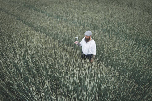 Drone shot of man holding small windmill while standing amidst cornfield - HMEF01008