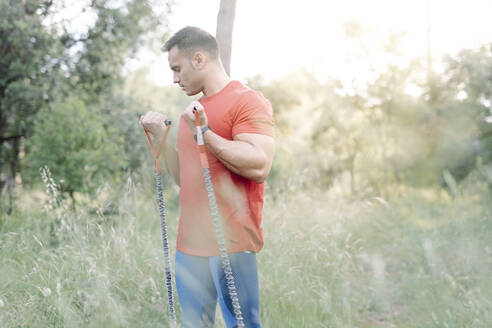 Man during workout with rubber ropes in the woods - JCZF00169
