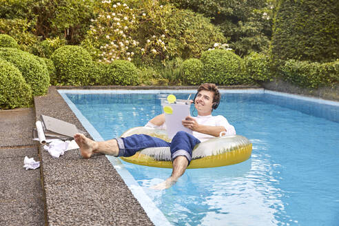 Young man sitting on airbed in swimmingpool and working - UKOF00002