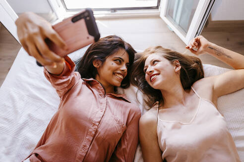 Friends looking at each other while taking selfie on bed at home - TCEF00806