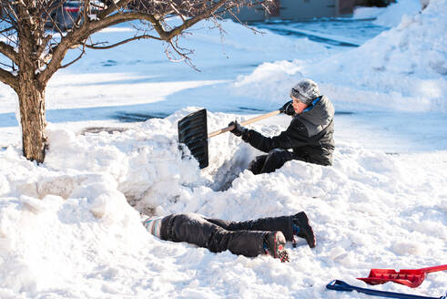 Two boys building snow forts with shovels on a sunny winter day. - CAVF86402