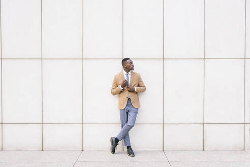 Young businessman leaning against a wall looking sideways - ABZF03212