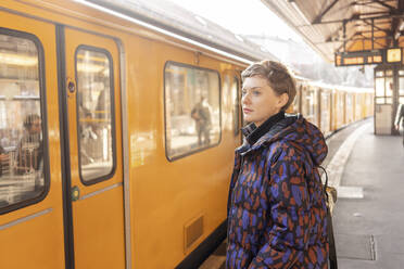 Portrait of woman waiting at platform, Berlin, Germany - TAMF02475