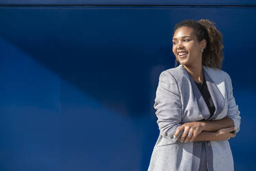 Smiling businesswoman in front of blue wall - SNF00431
