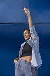 Smiling businesswoman with raised arm in front of blue wall - SNF00434