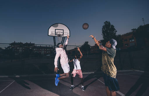 Male friends playing basketball in court against clear sky at night - OCMF01389